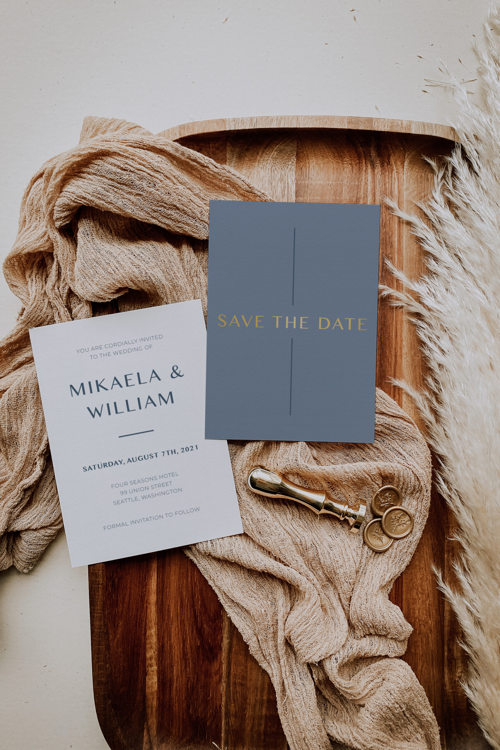 Dusty blue and gold foil save the date card with gold wax seals and pampas grass background
